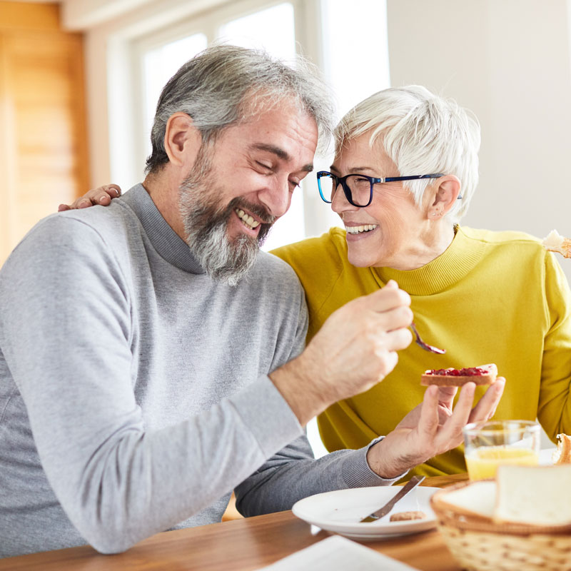 mature-couple-laughing-during-breakfast