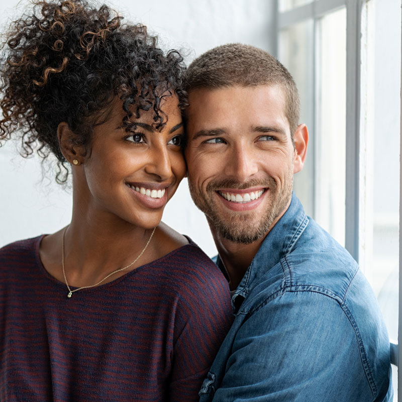 young-couple-looking-out-window-smiling